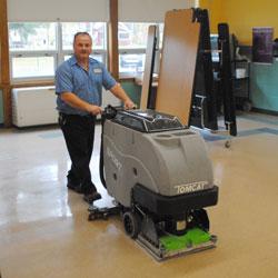 Custodian pushes floor polishing machine
