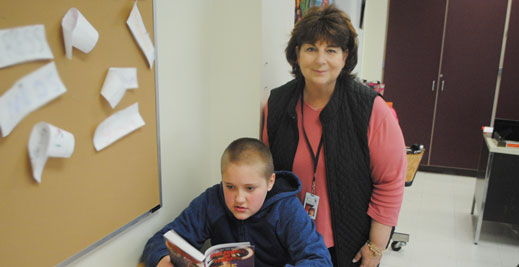 Teacher aide stands behind a student who is reading