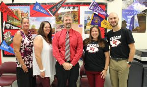 five school cpunseling staff members in a line smiling in front of bulletin board with college pennants