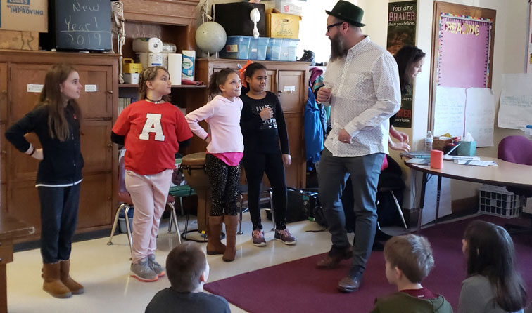 four girls dancing in classroom with instructor wearing fedora
