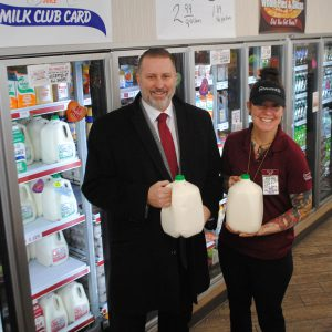 superintendent and Stewart's employee holding milk jugs msiling