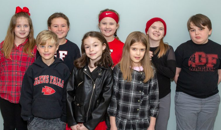 group of elementary students smiling in red and black clothing