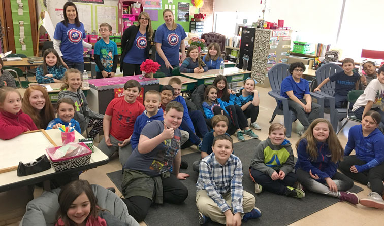 group of students and teachers in the classroom wearing blue
