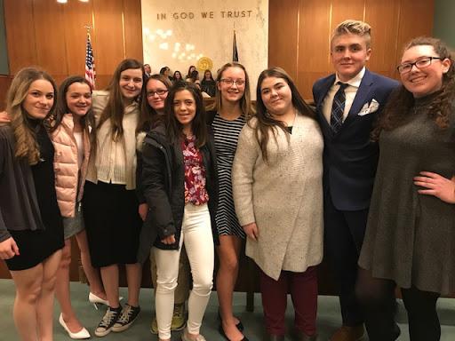 nine students smiling inside courtroom