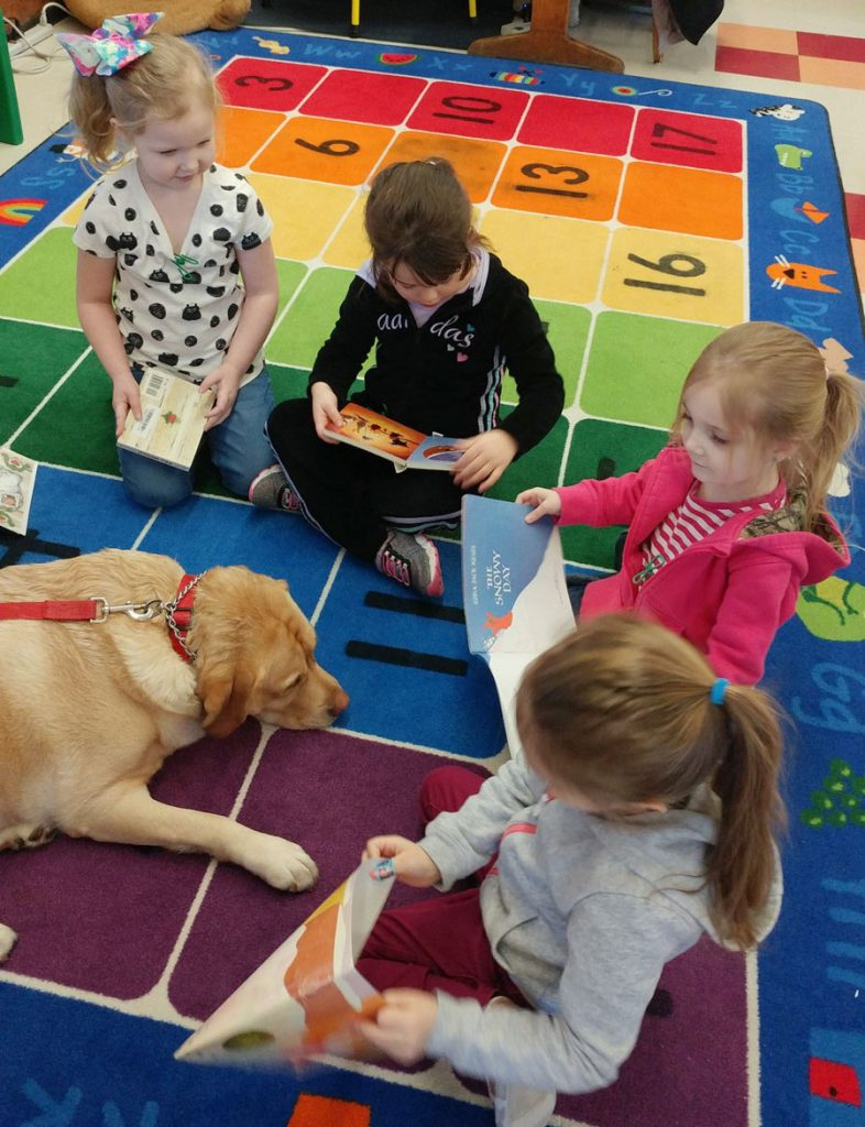 four pre-kindergarteners sitting on colorful rug with books beside yellow dog