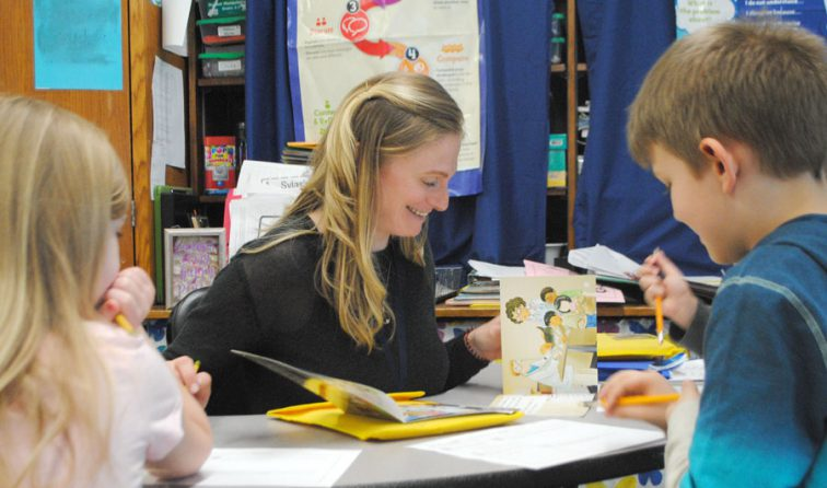 woman smiling while reading with elementary students