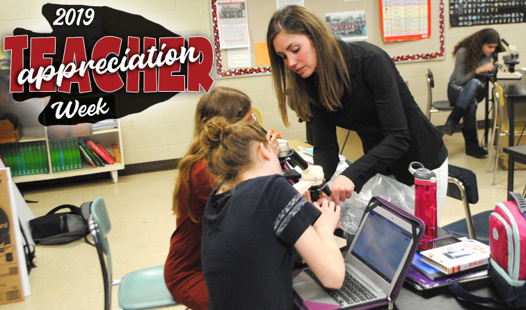 teacher instructing students with microscope and Chromebook