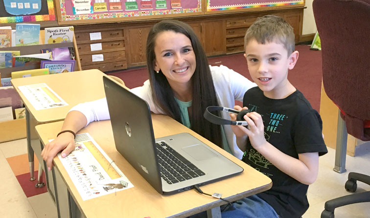 teacher and student smiling at desks