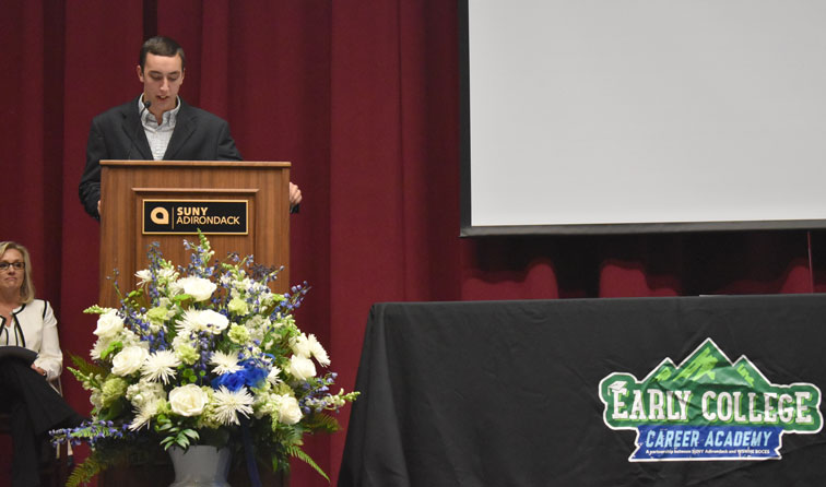 student at podium with flowers and logos for SUNY ADK and ECCA