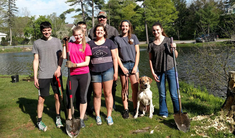 seven people standing in sunshine by pond holding shovels