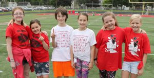 six elementary students on football field smiling with arms around each other