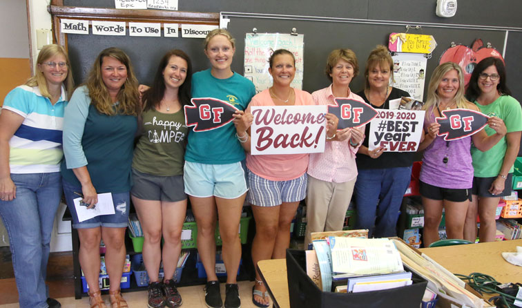 group of teachers smiling holding signs reading welcome back and best year ever 2019-2020