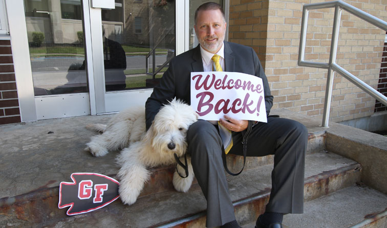 superintendent and therapy dog smiling holding signs reading welcome back