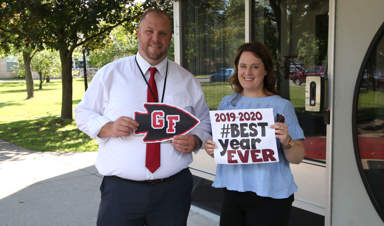 two teachers smiling holding signs reading welcome back and best year ever 2019-2020