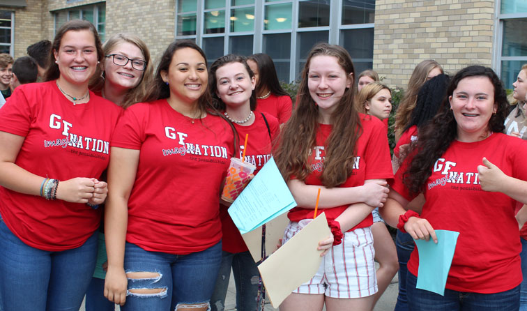 six students smiling in red GF Nation t-shirts outside school
