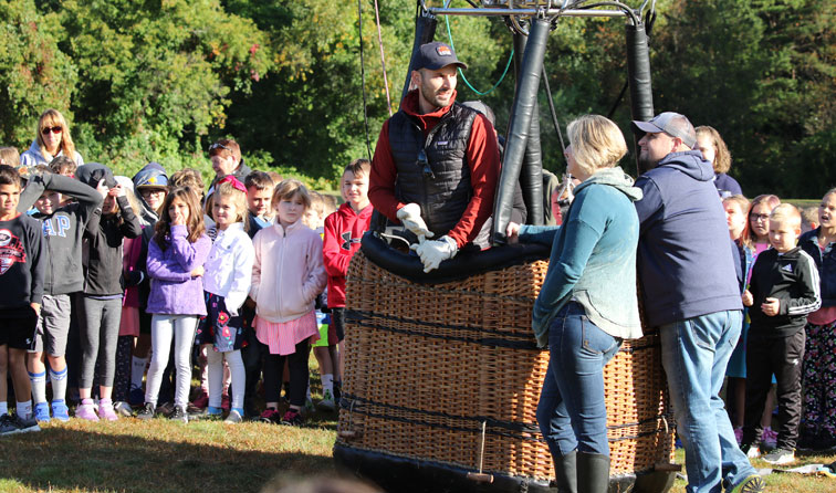 four people in and around a hot air balloon basket speaking to students gathered on a lawn