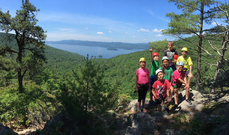 group of kids on top of mountain with sunny lake view in background