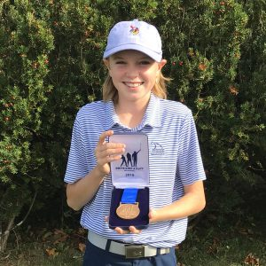 boy smiling holding golf medal in front of green trees