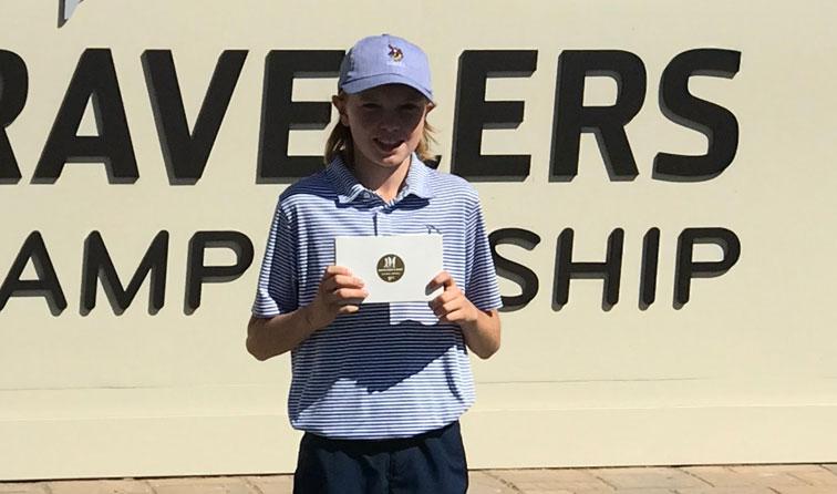 boy smiling holding golf medal