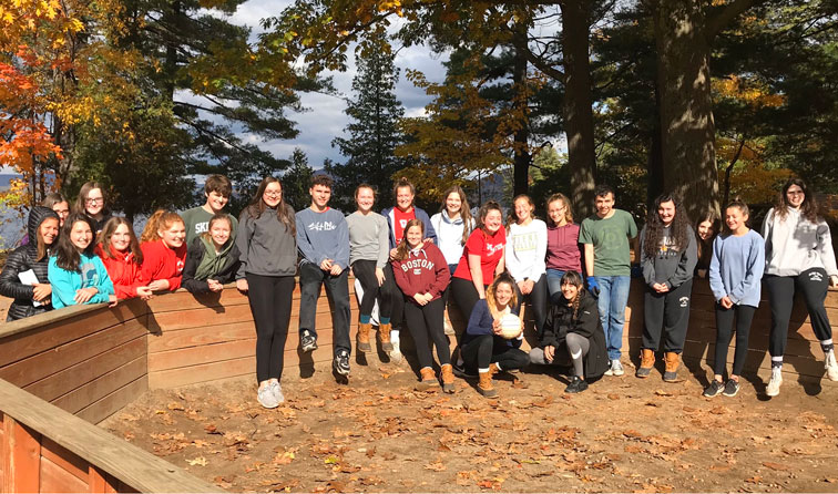 group of students smiling outside with fall forest in background