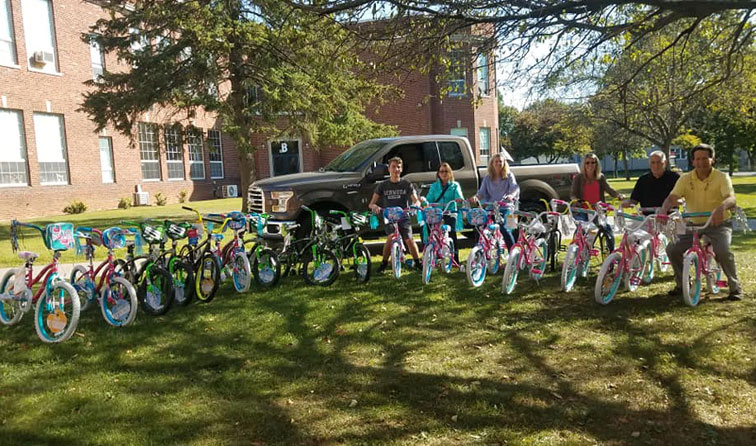 row of children's bikes on front lawn of school with six adults smiling