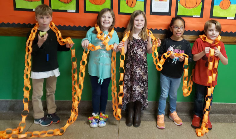 group of students smiling holding orange paper chains