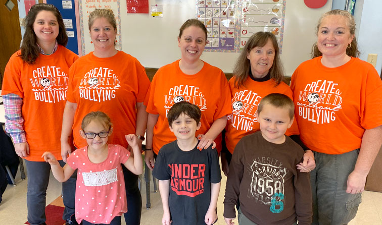 Eight teachers and students wearing orange anti-bullying tshirts, smiling