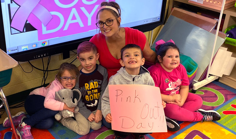 group of students smiling holding sign reading pink out day