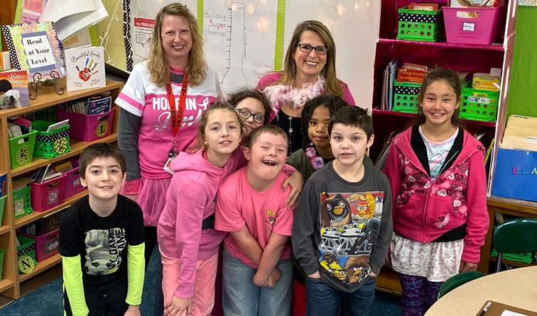 group of students together smiling, wearing pink for cancer awareness