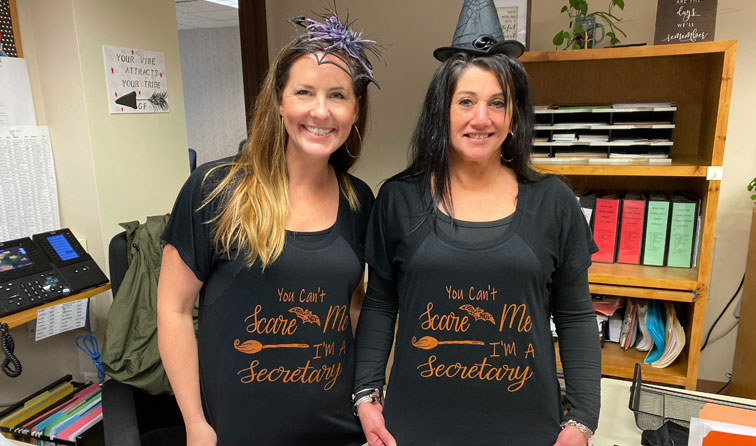 "two staff members dressed in Halloween shirts that read ""you can't scare me I'm a secretary"""
