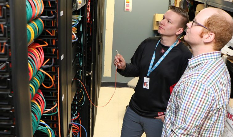 two people examining a server bank with colorful wires
