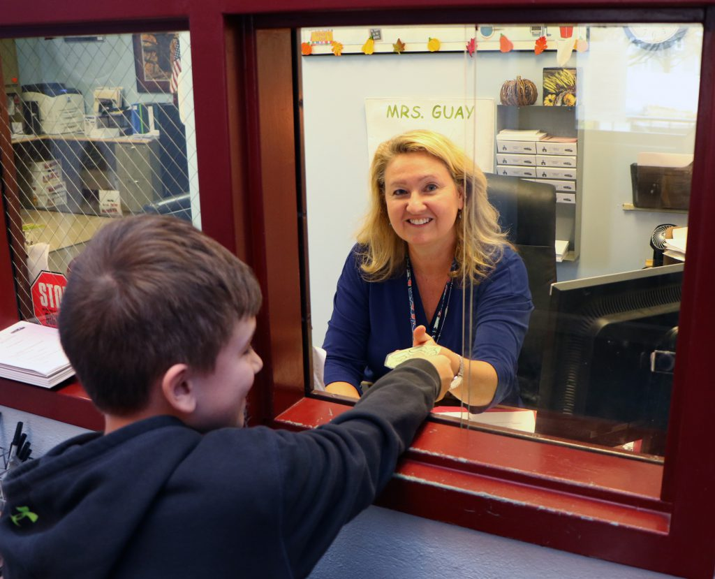 person smiling while handing a green turtle hall pass to a student through window
