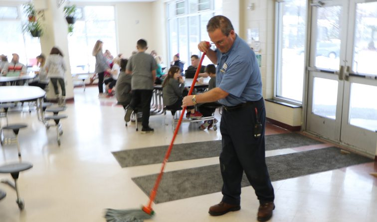 custodian mopping school cafeteria floor