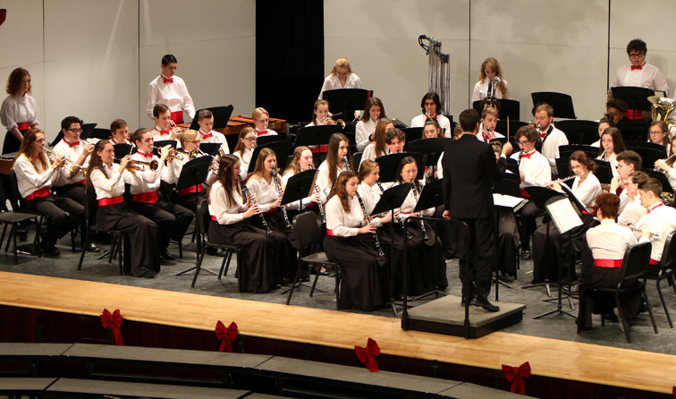large group of student musicians performing in band concert on stage wearing red cummerbunds