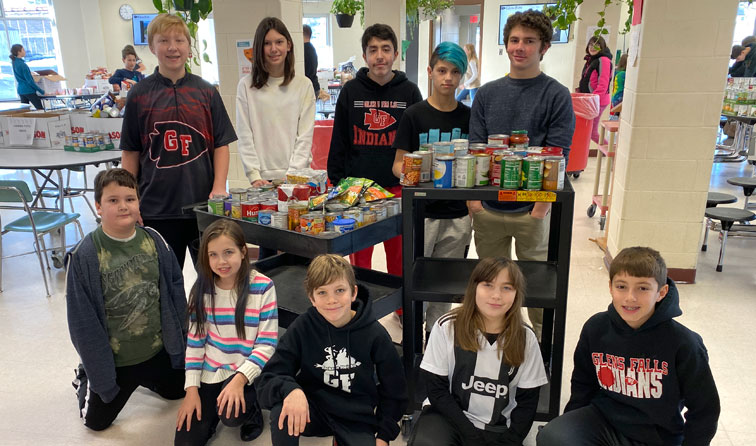 group of students smiling with carts of canned food