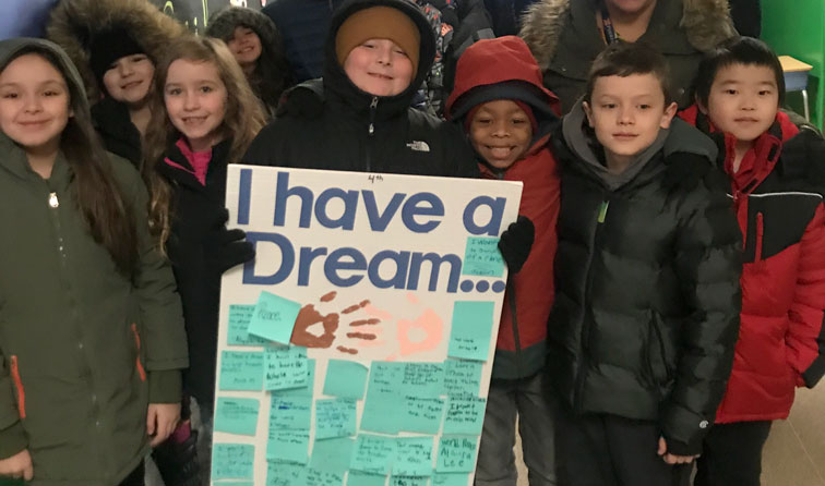 group of students smiling holding sign that says I have a Dream
