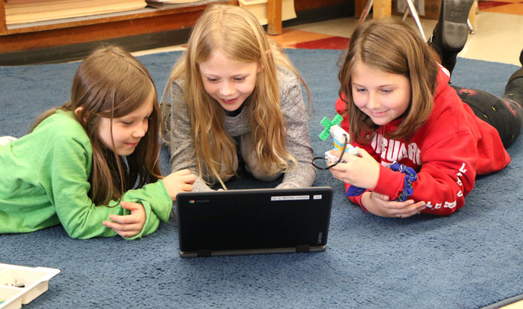 three students on classroom carpet with Chromebook and Lego windmill
