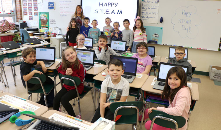 "classroom of students smiling with Chromebooks and ""happy steam day"" written on whiteboard"