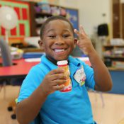 student in kindergarten classroom during snack time smiling with drink