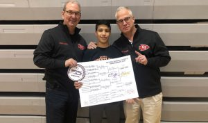 three people smiling with sectionals patch and championship bracket poster