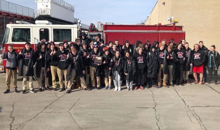 big group of student-athletes in front of fire truck holding sectionals plaque