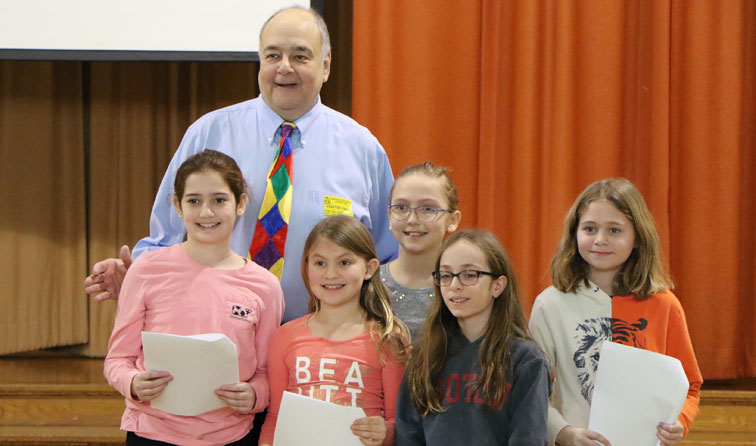 Author Alan Katz with smiling students performing a silly dilly song