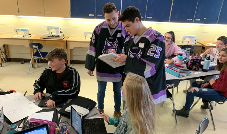 Two hockey players wearing jerseys sign notebook in classroom with students smiling