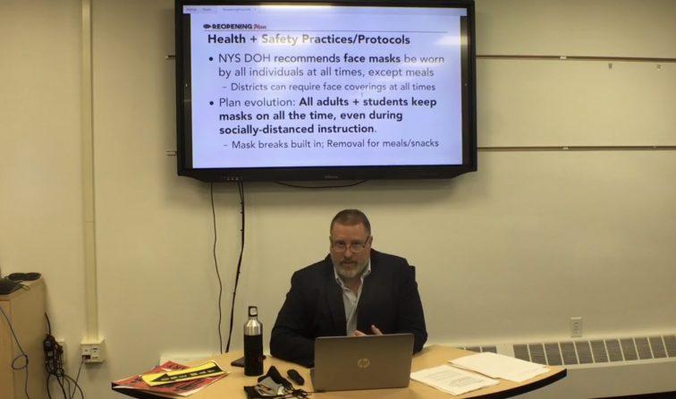 scfreenshot of reopening forum showing superintendent sitting before slideshow on TV