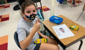 student at school desk with face mask coloring GF Nation strong artwork