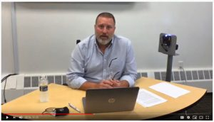 screen grab of superintendent talking with laptop on desk and temperature scanner on side during online parent forum