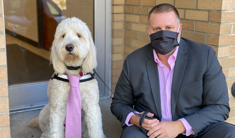Finnigan the golden-doodle wearing a pink tie, sitting next to Superintendent Jenkins wearing a pink shirt