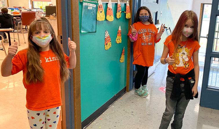 students wearing orange shirts, smiling