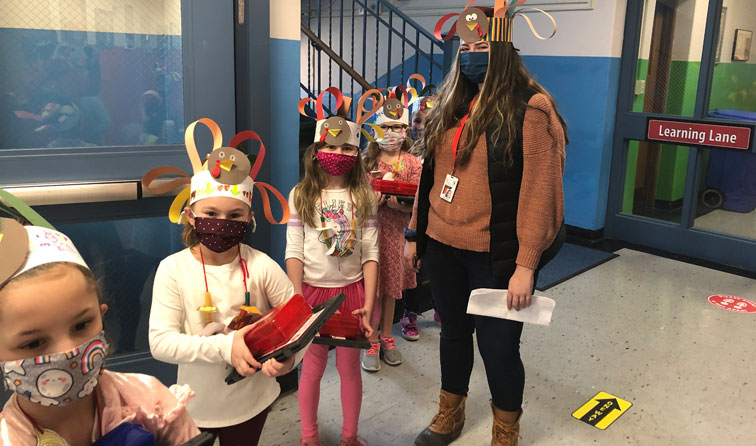 group of students in face masks with colorful construction paper turkey hats on heads