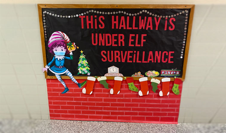 colorful bulletin board of elf wearing a mask, stockings hung at a fireplace and the text - this hallway is under elf surveillance
